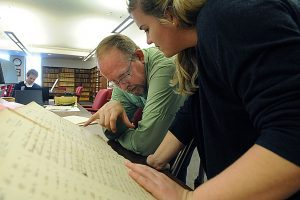 CHW team members Will Bosley (left) and Dani Callahan look over the Dix Hospital admissions ledger at the State Archives. (photo by Donn Young)