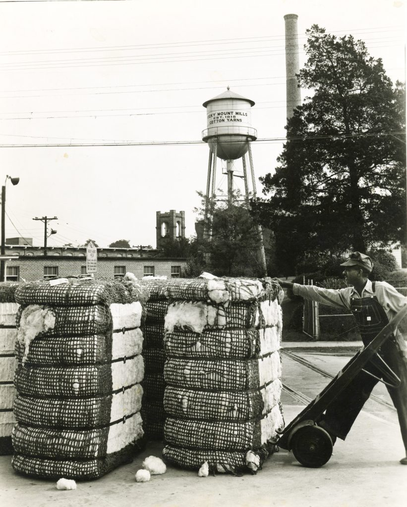 William Henry Summers lifting cotton bales outside the mill with a hand truck