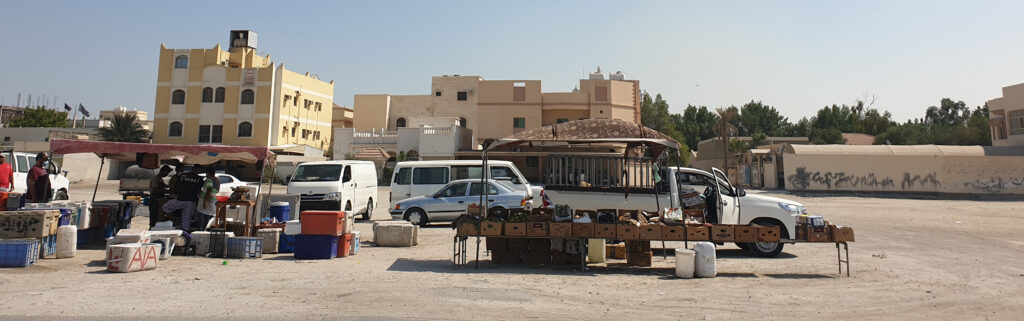 Bahrainis selling produce under the protective shade of tents